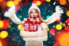 圣诞节和新年假日 拿着在冬天背景的惊奇的妇女礼物盒与在黑星期五,销售的雪 免版税库存照片