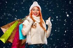 圣诞节和新年假日 拿着颜色袋子和在与雪的冬天背景的购物妇女在黑星期五 库存照片