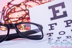 圣诞节和新年在眼科学视力测定方面 镜片和眼科桌视敏度的在前景测试与 免版税库存照片