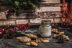 圣诞节和新年桌与诗歌选、曲奇饼、杉木锥体、wallnuts和蜡烛的装饰背景在杯子 免版税库存图片