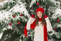 圣诞节和新年的概念 冬天震动 红色的女孩和在欢乐圣诞树附近的手套帽子 库存图片