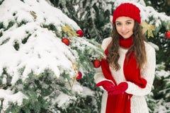 圣诞节和新年的概念 冬天震动 红色的女孩和在欢乐圣诞树附近的手套帽子 免版税图库摄影