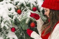 圣诞节和新年的概念 冬天震动 红色的女孩和在欢乐圣诞树附近的手套帽子 免版税库存图片