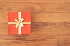 圣诞节和新年节日礼物箱子包裹与红色纸和黄色丝带在木台式的木桌面看法鞠躬 免版税库存图片