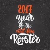圣诞节和新年字法书法贺卡与2017年在黑色的红火雄鸡 库存图片
