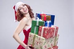 圣诞节和新年概念和想法 拿着大堆在手和微笑上的礼物盒的正面白种人雪未婚 库存图片