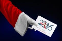 圣诞节和新年2016年题材:拿着在深蓝背景的圣诞老人手一白色礼品券在演播室被隔绝 免版税库存图片