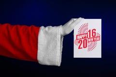 圣诞节和新年2016年题材:拿着在深蓝背景的圣诞老人手一白色礼品券在演播室被隔绝 免版税库存照片