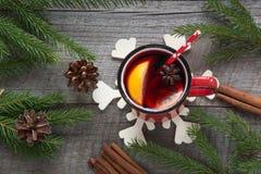 圣诞节和欢乐被仔细考虑的酒在一个红色杯子用香料,桂香,八角,锥体,冷杉分支在一张土气木桌上 克里斯 库存图片