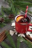 圣诞节和欢乐被仔细考虑的酒在一个红色杯子用香料,桂香,八角,锥体,冷杉分支在一张土气木桌上 免版税库存照片