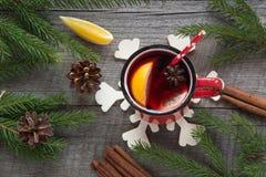 圣诞节和欢乐被仔细考虑的酒在一个红色杯子用香料,桂香,八角,锥体,冷杉分支在一张土气木桌上 克里斯 免版税图库摄影