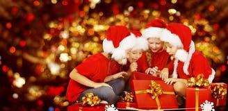 圣诞节哄骗打开的当前礼物盒,圣诞老人帽子的孩子 免版税库存照片
