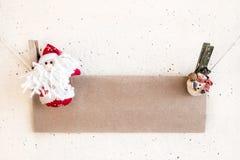 圣诞节圣诞老人和拿着工艺纸的雪人晒衣夹 免版税库存照片
