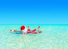 圣诞节圣诞老人在海洋绿松石透明水中放松游泳 库存照片