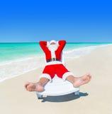 圣诞节圣诞老人在sunlounger放松在海洋完善的海滩 库存图片