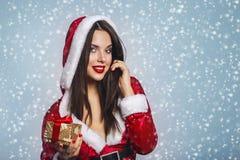 圣诞节圣诞老人帽子妇女画象举行圣诞节礼物盒 蓝色背景的微笑的愉快的女孩 性感美丽的女孩的纵向 免版税图库摄影