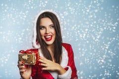 圣诞节圣诞老人帽子妇女画象举行圣诞节礼物盒 蓝色背景的微笑的愉快的女孩 性感美丽的女孩的纵向 免版税库存照片