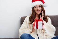 圣诞节圣诞老人帽子查出妇女纵向暂挂圣诞节礼品 免版税图库摄影