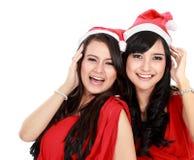 圣诞节圣诞老人帽子的两个女孩获得乐趣 库存图片