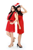 圣诞节圣诞老人帽子的两个女孩获得乐趣 免版税库存图片