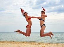 圣诞节圣诞老人帽子的两个美丽的女孩在海滩 库存照片