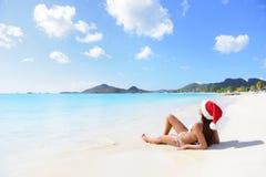 圣诞节圣诞老人帽子的海滩妇女在比基尼泳装 库存照片