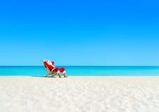 圣诞节圣诞老人棕褐色放松在沙滩的sunlounger 图库摄影