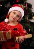 圣诞节圣诞老人的帽子的逗人喜爱的做鬼脸的孩子女孩对负 免版税库存照片