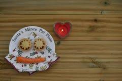 圣诞节圣诞老人的摄影图象肉馅饼板材用百果馅酥皮点心饼和红萝卜驯鹿的在木背景 免版税库存照片