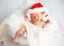 圣诞节圣诞老人盖帽的睡眠者新出生的婴孩 免版税库存照片