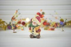 圣诞节圣诞节装饰愉快的雪人的摄影图象有在白色木头的闪耀的金子xmas背景 库存照片