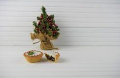 圣诞节圣诞节食物的摄影图象肉馅饼和微型玩具树有自然白色木背景 免版税库存图片