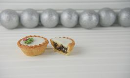 圣诞节圣诞节食物的摄影图象肉馅饼和银闪烁中看不中用的物品在白色木背景 免版税库存图片