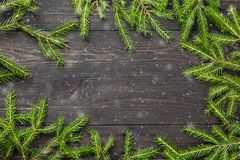 圣诞节在一个黑暗的木板的杉树有雪的 您的项目的圣诞节或新年框架与拷贝空间 库存图片