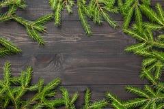 圣诞节在一个黑暗的木板的杉树 您的项目的圣诞节或新年框架与拷贝空间 库存图片