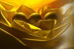 圣诞节在一块黄色缎布料的球装饰 免版税库存图片