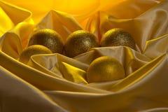 圣诞节在一块黄色缎布料的球装饰 免版税库存照片