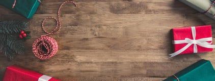 圣诞节在一张木桌,横幅边界设计背景上的礼物盒 库存图片