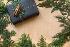 圣诞节在与装饰的黑纸包裹的礼物盒在木表面上的分支柏附近 土气样式 免版税库存图片
