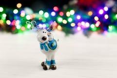 圣诞节在五颜六色的诗歌选背景的驯鹿玩具点燃 图库摄影