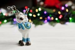 圣诞节在五颜六色的诗歌选背景的驯鹿玩具点燃 库存照片
