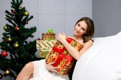 圣诞节在俏丽的结构树附近的礼品女&# 免版税库存照片