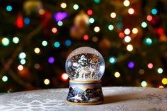 圣诞节在圣诞树前面的雪地球点燃特写镜头 免版税图库摄影