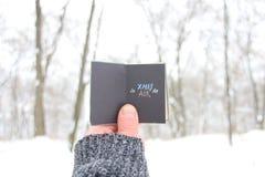 圣诞节在天空中,拿着与题字的人一本书 图库摄影