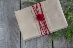 圣诞节在木桌,包裹的工艺品,羊皮纸,麻线,杉树枝杈,逗人喜爱的简单的最后一刻的当前handmad上的礼物盒 免版税库存图片