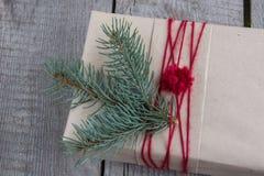 圣诞节在木桌,包裹的工艺品,羊皮纸,麻线,杉树枝杈,逗人喜爱的简单的最后一刻的当前handmad上的礼物盒 库存照片