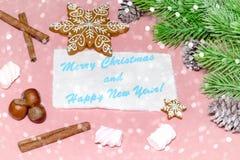 圣诞节在木浅粉红色的桌的贺卡与雪杉树、雪花、坚果、蛋白软糖和cinamon 免版税图库摄影