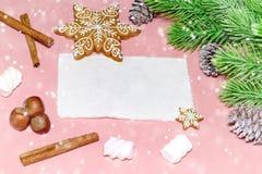 圣诞节在木浅粉红色的桌的贺卡与雪杉树、雪花、坚果、蛋白软糖和cinamon 库存图片