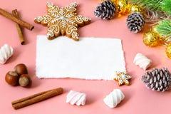 圣诞节在木浅粉红色的桌的贺卡与雪杉树、雪花、坚果、蛋白软糖和cinamon 库存照片