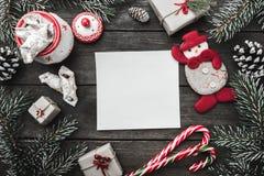 圣诞节在木背景,冷杉的贺卡分支,锥体,雪人,给圣诞老人的信件与寒假消息  免版税库存照片